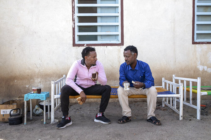 Surgeon and doctor-turned-refugee, Dr. Tewodros Tefera, right, drinks tea and eats breakfast with a friend before starting his workday, at the Sudanese Red Crescent clinic where he takes shelter and works, in Hamdayet, eastern Sudan, near the border with Ethiopia, on March 22, 2021. (AP Photo/Nariman El-Mofty)