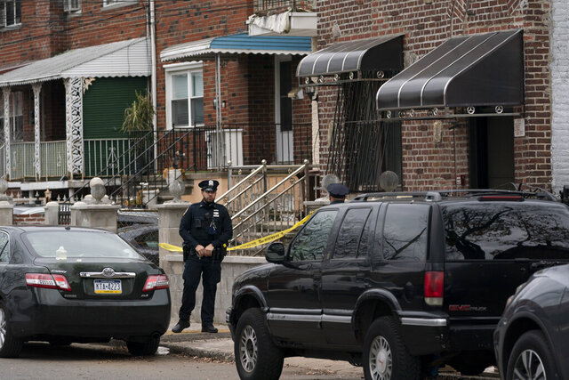 A police officer stands watch in front of a house, right, which was the scene of a shooting in The Bronx, Friday, Dec. 4, 2020 in New York. A suspect in the shooting of a state trooper in Massachusetts was killed during a shootout with U.S. marshals in New York City early Friday that left two of the officers wounded. (AP Photo/Mark Lennihan)