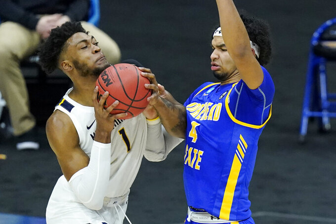 West Virginia's Derek Culver (1) drives against Morehead State's Johni Broome (4) during the first half of a college basketball game in the first round of the NCAA tournament at Lucas Oil Stadium Friday, March 19, 2021, in Indianapolis. (AP Photo/Mark Humphrey)