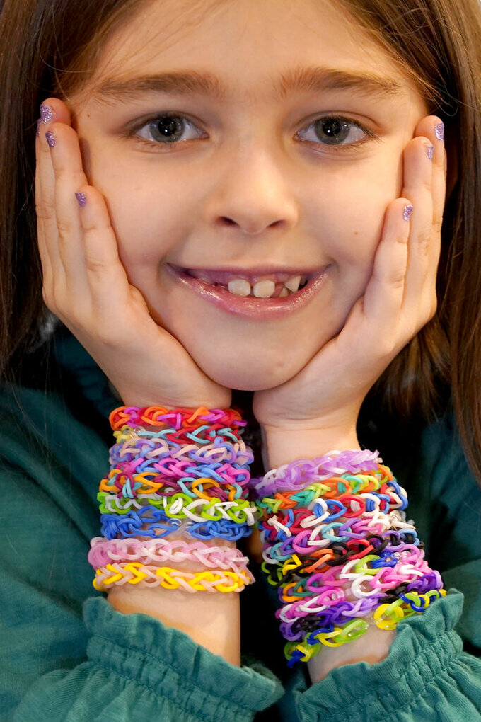 Hayley Orlinsky poses for a portrait Wednesday, Dec. 2, 2020, with several colorful rubber band bracelets she makes in her Chicago home. The 7-year-old has spent most of the coronavirus pandemic crafting the bracelets as a fundraiser, earning nearly $20,000, to buy personal protective equipment for the Ann and Robert H. Lurie Children's Hospital. (AP Photo/Charles Rex Arbogast)