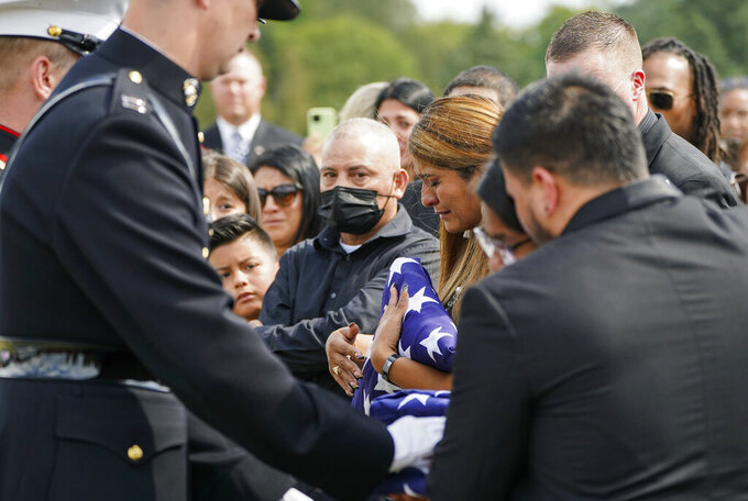 The family of Marine Cpl. Humberto Sanchez are presented folded flags during the graveside service at Mount Hope Cemetery in Logansport, Ind., on Tuesday, Sept. 14, 2021. Sanchez was one of 13 U.S. service members killed in last month's suicide bombing at Afghanistan's Kabul airport during the U.S.-led evacuation.  (Jonah Hinebaugh/The Pharos-Tribune via AP)
