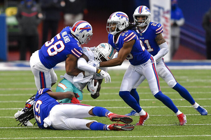 Miami Dolphins wide receiver DeVante Parker (11) is tackled by Buffalo Bills middle linebacker Tremaine Edmunds (49) and outside linebacker Matt Milano (58) in the second half of an NFL football game, Sunday, Jan. 3, 2021, in Orchard Park, N.Y. (AP Photo/Adrian Kraus)