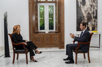 In this photo released on Monday Nov. 9, 2019 by the Syrian official news agency SANA, Syrian President Bashar Assad, right, speaks during an interview with Monica Maggioni, left, the CEO of Italy's Rai News 24, in Damascus, Syria. Assad said in an interview aired Monday that the global chemical weapons watchdog has faked and falsified a report over an attack near the capital Damascus last year