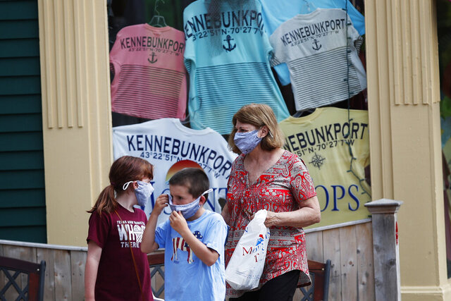 Visitors walk by a souvenir t-shirt shop Tuesday, June 23, 2020, in Kennebunkport, Maine. The coronavirus pandemic has hurt many of Maine's businesses that rely on just a few months in the summer for most of their annual revenue. (AP Photo/Robert F. Bukaty)