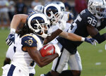 Los Angeles Rams' Nsimba Webster, left, rushes against the Oakland Raiders during the second half of a preseason NFL football game Saturday, Aug. 10, 2019, in Oakland, Calif. (AP Photo/Rich Pedroncelli)