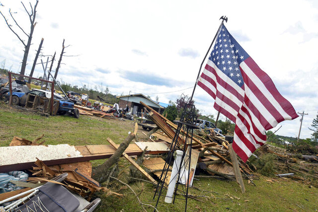 Laurel homeowner Mike Kelley placed an American flag in his yard after a tornado hit his Matthews Community home Easter Sunday, Friday, April 17, 2020 in Jackson, Miss.(Cam Bonelli/Hattiesburg American via AP)