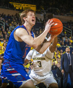 Presbyterian forward Owen McCormack, front, attempts a basket defended by Michigan guard Zavier Simpson (3) in the first half of an NCAA college basketball game at Crisler Center in Ann Arbor, Mich., Saturday, Dec. 21, 2019. (AP Photo/Tony Ding)