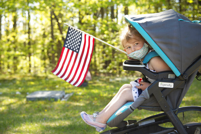 Anna Wines, 3, of Bath, Maine, helps carry American flags while her family places new flags next to the gravestone of each veteran at Riverside Cemetery in Lewiston, Maine, Thursday, May 21, 2020. Volunteers will place nearly 7,500 new flags near veterans' graves at the 13 cemeteries across Lewiston, Maine, by Memorial Day. (Daryn Slover/Sun Journal via AP)