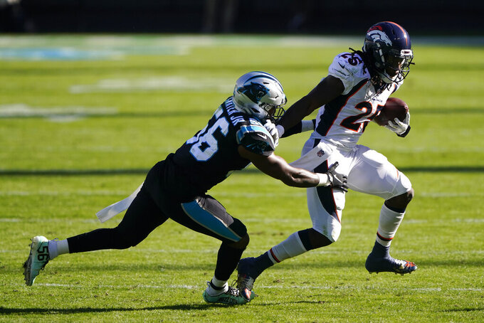 Denver Broncos running back Melvin Gordon III breaks away from Carolina Panthers linebacker Jermaine Carter during the first half of an NFL football game Sunday, Dec. 13, 2020, in Charlotte, N.C. (AP Photo/Brian Blanco)