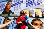 U.S. Rep. Alexandria Ocasio-Cortez, D, New York, center, speaks to members of the media while standing beside a truck plastered with campaign posters after greeting voters in Astoria, Queens, Tuesday, June 23, 2020, on primary election day in New York. (AP Photo/Kathy Willens)