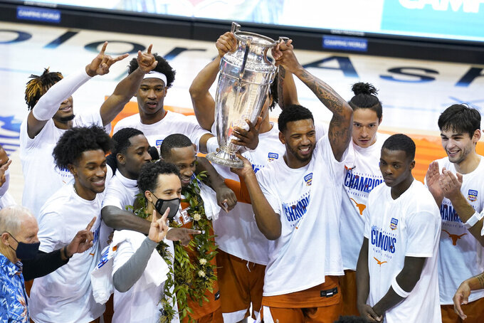 Texas celebrates and holds the trophy for the NCAA college basketball game championship of the Maui Invitational after they beat North Carolina 69-67, Wednesday, Dec. 2, 2020, in Asheville, N.C. (AP Photo/Kathy Kmonicek)