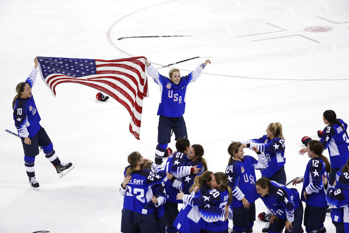 FILE - In this Feb. 22, 2018, file photo, Meghan Duggan (10), of the United States, and Monique Lamoureux-Morando (7), also of the United States, celebrate with teammates after defeating Canada in the women's gold medal hockey game at the Winter Olympics in Gangneung, South Korea. U.S. women's hockey captain Duggan announced her retirement Tuesday, Oct. 13, 2020, after a career in which she won the 2018 Olympic gold medal and seven world championship golds. (AP Photo/Matt Slocum, File)