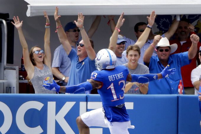 Kansas cornerback Hasan Defense celebrates in front of fans after returning an interception for a touchdown during the first half of an NCAA college football game against Indiana State, Saturday, Aug. 31, 2019, in Lawrence, Kan. (AP Photo/Charlie Riedel)