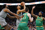 Brooklyn Nets guard Timothe Luwawu-Cabarrot (9) drives to the basket against Boston Celtics forward Gordon Hayward (20) and guard Brad Wanamaker (9) during the first half of an NBA basketball game Tuesday, March 3, 2020, in Boston. (AP Photo/Mary Schwalm)