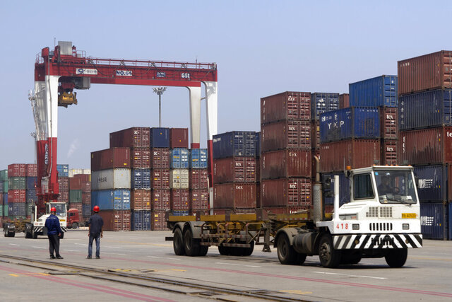 In this July 24, 2019, file photo, workers watch as a truck passes by stacks of shipping containers at a port in Yingkou in northeastern China's Liaoning Province. Authorities in China's rust-belt region are looking for support for its revival from Beijing's multibillion-dollar initiative to build ports, railways and other projects abroad. (AP Photo/Olivia Zhang)