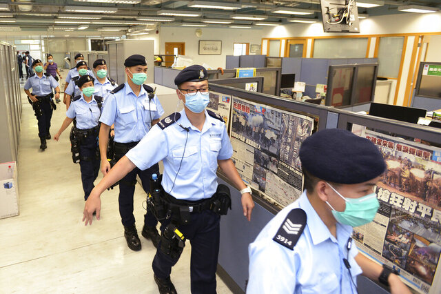 In this Monday, Aug. 10, 2020, photo, police officers take enter the Apple Daily newspaper headquarters as founder Jimmy Lai is arrested by police officers at his home in Hong Kong. Seven human rights experts affiliated with the U.N. raised concerns over Hong Kong's national security law in a letter addressed to Chinese authorities, saying that the law infringed on certain fundamental rights. (Apple Daily via AP)