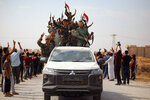 In this photo released by the Syrian official news agency SANA, people welcome Syrian troops as they enter the town of Ein Issa, north of Raqqa, Syria, Monday, Oct 14, 2019. Syrian troops moved east from Aleppo province to Raqqa where state media said they had reached Ein Issa. Heavy fighting the previous day there reached a Kurdish-run displaced-person camp that is home to some 12,000 people, including around 1,000 wives and widows of IS fighters and their children. Hundreds are believed to escaped amid the chaos. (SANA via AP)