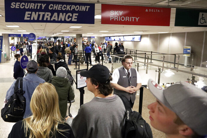 FILE - In this Wednesday, Nov. 27, 2019, file photo, travelers walk through a security checkpoint in Terminal 2 at Salt Lake City International Airport, in Salt Lake City. Federal officials are considering requiring that all travelers, including American citizens, be photographed as they enter or leave the country as part of an identification system using facial-recognition technology. (AP Photo/Rick Bowmer, File)