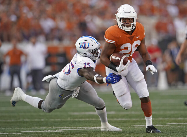 FILE - In this Saturday, Oct. 19, 2019 file photo, Texas's Keaontay Ingram (26) runs through a tackle of Kansas's Kyron Johnson (15) during the first half of an NCAA college football game in Austin, Texas. Running back Keaontay Ingram is transferring from Texas to Southern California. USC confirmed the latest addition to its backfield Tuesday, Jan. 26, 2021.(AP Photo/Chuck Burton, File)