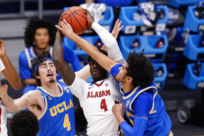 Alabama forward Juwan Gary (4) protects the ball from UCLA guard Johnny Juzang (3) and Jaime Jaquez Jr. (4) in the first half of a Sweet 16 game in the NCAA men's college basketball tournament at Hinkle Fieldhouse in Indianapolis, Sunday, March 28, 2021. (AP Photo/AJ Mast)