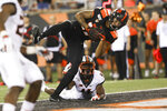 Oregon State wide receiver Isaiah Hodgins (17) lands in the endzone over Oklahoma State cornerback A.J. Green (4) to score a touchdown during the second half of an NCAA college football game with Oregon State in Corvallis, Ore., Friday, Aug. 30, 2019. Oklahoma State won 52-36. (AP Photo/Amanda Loman)
