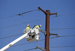 Workers repair a power line adjacent to the site of a fatal balloon crash in Albuquerque, N.M., Saturday, June 26, 2021.  Multiple people were killed in the crash.  (AP Photo/Andres Leighton)