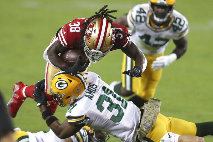 San Francisco 49ers running back JaMycal Hasty (38) is tackled by Green Bay Packers strong safety Adrian Amos (31) during the first half of an NFL football game in Santa Clara, Calif., Thursday, Nov. 5, 2020. (AP Photo/Jed Jacobsohn)