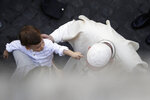 A child reaches out to Pope Francis as he greets faithful in the St. Damaso courtyard on the occasion of the weekly general audience at the Vatican, Wednesday, Sept. 16, 2020. (AP Photo/Gregorio Borgia)
