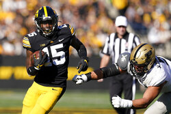 Iowa running back Tyler Goodson (15) runs from Purdue defensive end George Karlaftis, right, during the first half of an NCAA college football game, Saturday, Oct. 16, 2021, in Iowa City, Iowa. (AP Photo/Charlie Neibergall)