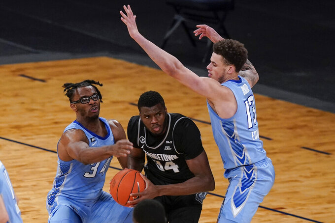 Georgetown's Qudus Wahab (34) protects the ball from Creighton's Denzel Mahoney (34) and Christian Bishop (13) during the second half of an NCAA college basketball game in the championship of the Big East Conference tournament Saturday, March 13, 2021, in New York. (AP Photo/Frank Franklin II)