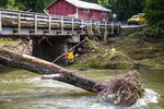 NCDOT workers assess damage to a bridge spanning the Pigeon River, Thursday, Aug. 19, 2021, in Bethel, N.C., after remnants from Tropical Storm Fred caused flooding in parts of Western North Carolina Tuesday. Search and rescue teams continue to search the area as 20 people are missing and 2 people were found dead. (Travis Long/The News & Observer via AP)