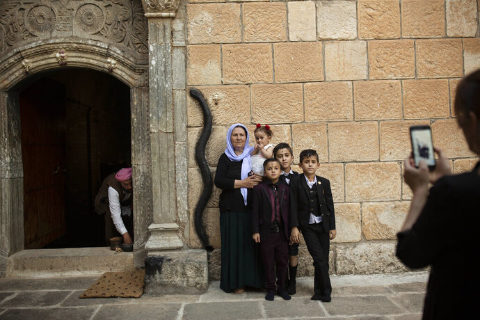 In this Aug. 23, 2019 photo, a Yazidi family poses for a photo at the door to the Lalish temple near Sheikhan, Iraq. The ancient sect is rebuilding, nearly six years after Islamic State militants launched its coordinated attack on the heartland of the Yazidi community at the foot of Sinjar Mountain in August 2014. (AP Photo/Maya Alleruzzo)
