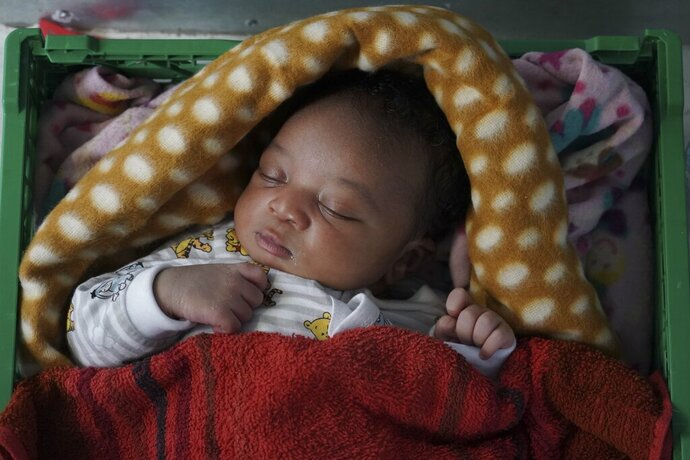 Ange, a 5-day-old newborn baby from Cameroon sleeps inside the women's shelter of the Ocean Viking humanitarian rescue ship in the Mediterranean Sea, Wednesday, Sept. 18, 2019. The baby, his mother and two brothers were among 109 people rescued on Tuesday by the Norwegian-flagged ship operated by SOS Mediterranee and Doctors Without Borders. (AP Photo/Renata Brito)
