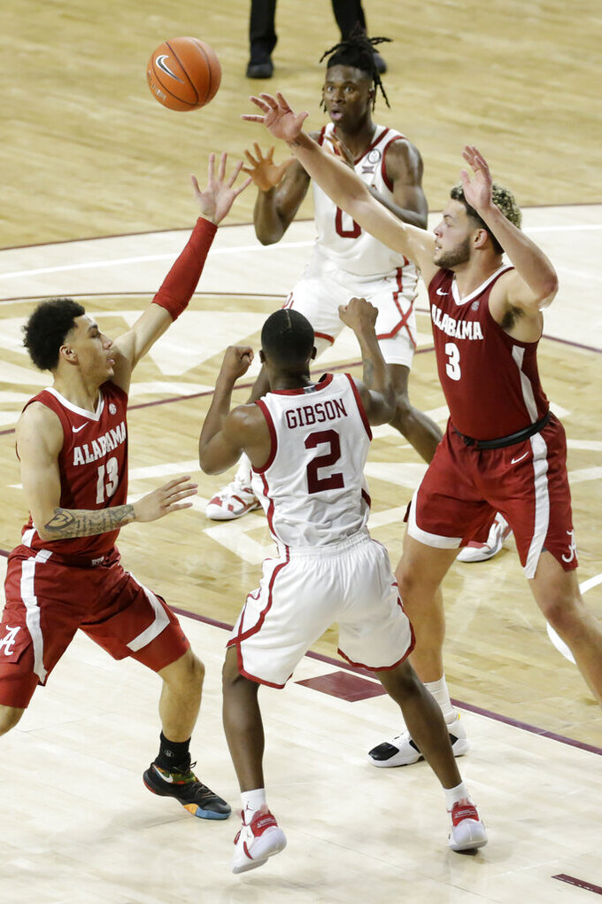Oklahoma's Umoja Gibson (2) passes the ball to Victor Iwuakor (0) away from Alabama's Jahvon Quinerly (13) and Alex Reese (3) during the second half of an NCAA college basketball game in Norman, Okla., Saturday, Jan. 30, 2021. (AP Photo/Garett Fisbeck)