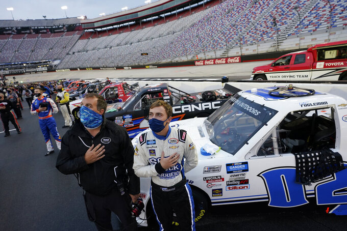 Tate Fogleman, front right, puts his hand over his heart during the national anthem before the NASCAR Truck Series auto race Thursday, Sept. 17, 2020, in Bristol, Tenn. (AP Photo/Steve Helber)