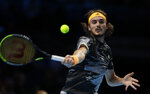 Stefanos Tsitsipas of Greece plays a return to Roger Federer of Switzerland during their ATP World Tour Finals semifinal tennis match at the O2 Arena in London, Saturday, Nov. 16, 2019. (AP Photo/Kirsty Wigglesworth)