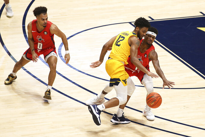 West Virginia guard Taz Sherman (12) is defended by Richmond guards Jacob Gilyard (0) and Blake Francis (1) during the second half of an NCAA college basketball game Sunday, Dec. 13, 2020, in Morgantown, W.Va. (AP Photo/Kathleen Batten)