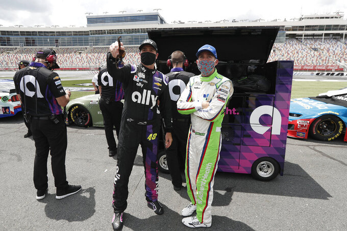 Drivers Jimmie Johnson, left, and Ross Chastain watch along pit road during qualifying for a NASCAR Cup Series auto race at Charlotte Motor Speedway Sunday, May 24, 2020, in Concord, N.C. (AP Photo/Gerry Broome)
