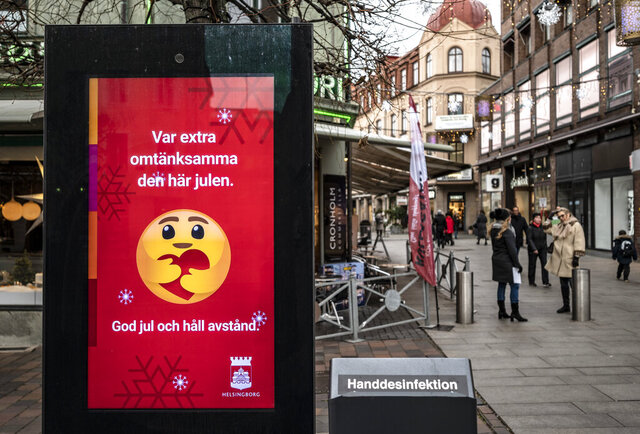 An public information sign wishing Merry Christmas and asking to maintain social distancing is seen in a pedestrian shopping street in Helsingborg, southern Sweden, on Monday Dec. 7, 2020. The last week in November, Helsingborg had more new confirmed Covid-19 cases than in any other city in Sweden, according to official figures. (Johan Nilsson / TT via AP)
