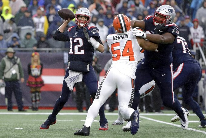 New England Patriots quarterback Tom Brady, left, passes under pressure from Cleveland Browns defensive end Olivier Vernon in the first half of an NFL football game, Sunday, Oct. 27, 2019, in Foxborough, Mass. (AP Photo/Steven Senne)
