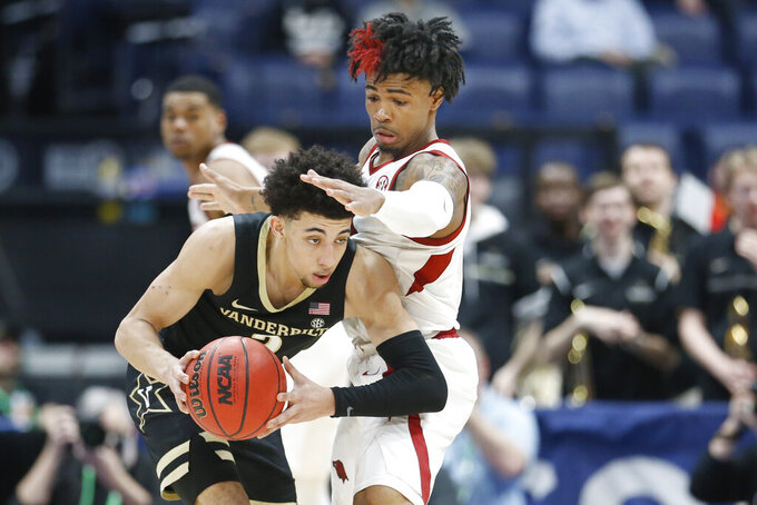 Vanderbilt's Scotty Pippen Jr., left, looks for a way past Arkansas guard Desi Sills in the second half of an NCAA college basketball game in the Southeastern Conference Tournament Wednesday, March 11, 2020, in Nashville, Tenn. Arkansas won 86-73. (AP Photo/Mark Humphrey)