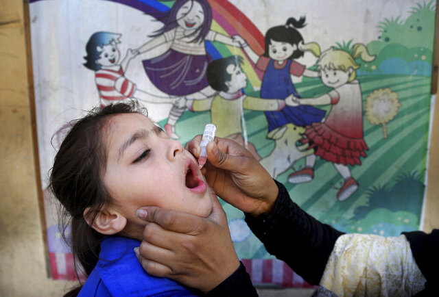 A health worker gives a polio vaccine to a child at a school in Lahore, Pakistan, Monday, Feb. 17, 2020. Pakistan government launched an anti-polio vaccination campaign in an effort to eradicate the crippling disease affected children. (AP Photo/K.M. Chaudary)