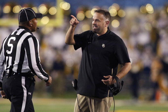 Baylor head coach Matt Rhule, right, complains to the referees during the second half of an NCAA college football game against West Virginia, Thursday, Oct. 25, 2018, in Morgantown, W.Va. (AP Photo/Raymond Thompson)