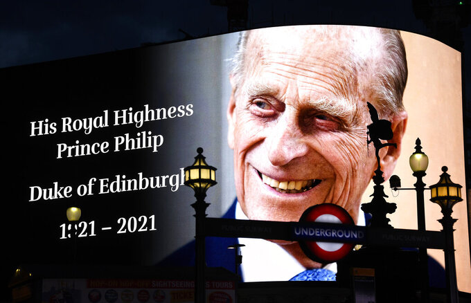 A tribute to Britain's Prince Philip is projected onto a large screen at Piccadilly Circus in London, Friday, April 9, 2021. Buckingham Palace officials say Prince Philip, the husband of Queen Elizabeth II, has died. He was 99. Philip spent a month in hospital earlier this year before being released on March 16 to return to Windsor Castle. (AP Photo/Alberto Pezzali)