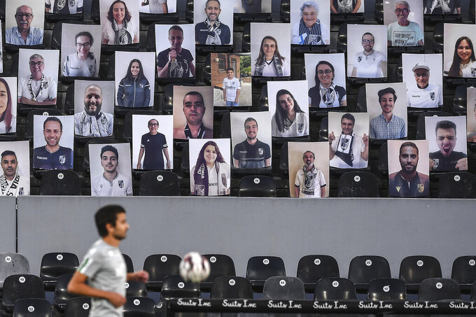 Vitoria de Guimaraes' supporters photos are placed from the stands prior of the Portuguese League soccer match between Vitoria SC and Sporting CP in Guimaraes, Portugal, Thursday, June 4, 2020. The Portuguese League soccer matches resumed Wednesday without spectators because of the coronavirus pandemic. (Hugo Delgado/Pool via AP)