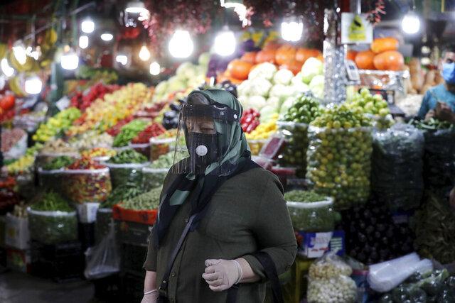 Una mujer con mascarilla, cubrebocas y guantes por el coronavirus, camina por el mercado Tajrish, en Teherán, Irán, el 15 de octubre de 2020. (AP Foto/Ebrahim Noroozi)