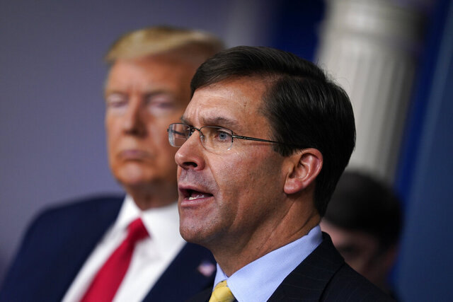 FILE - In this March 18, 2020, file photo, Defense Secretary Mark Esper speaks as President Donald Trump listens during press briefing with the coronavirus task force, at the White House in Washington. The government's $3 trillion effort to rescue the economy from the coronavirus crisis is stirring worry at the Pentagon. Bulging federal deficits may force a reversal of years of big defense spending gains and threaten prized projects like the rebuilding of the nation's arsenal of nuclear weapons. Esper says the sudden burst of emergency spending to prop up a stalled economy is bringing the Pentagon closer to a point where it will have to shed older weapons faster and tighten its belt. (AP Photo/Evan Vucci, File)