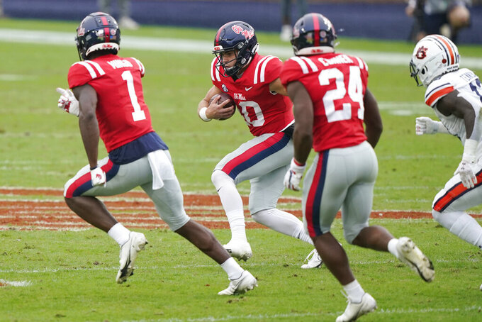 Mississippi quarterback John Rhys Plumlee (10) follows his blockers wide receiver Jonathan Mingo (1) and running back Snoop Conner (24) as he runs past Auburn defenders during the first half of an NCAA college football game in Oxford, Miss., Saturday Oct. 24, 2020. (AP Photo/Rogelio V. Solis)