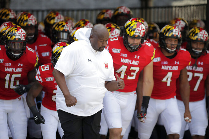 Maryland head coach Michael Locksley, center, leads his team onto the field for an NCAA college football game against Howard, Saturday, Aug. 31, 2019, in College Park, Md. (AP Photo/Julio Cortez)