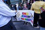 A young girl holds a poster she made as she prepares to pose for a cell phone photograph for a relative as she and others joined protesters outside the offices of New York Gov. Andrew Cuomo, Thursday, Oct. 15, 2020, in New York. Three Rockland County Jewish congregations are suing New York state and Cuomo, saying he engaged in a